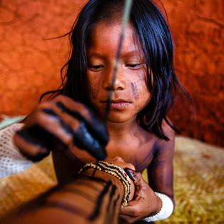 """Iraruti.  Essa pequena Kayapó costuma treinar sua pintura tradicional em bonecas, cabaças e abóboras. O talo de Inajá é o """"pincel"""" que garante um traço preciso e simétrico. De uma delicadeza sem igual e técnica quase tão aguçada quanto a dos adultos, hoje a """"tela"""" para esse treino precioso fui eu"""