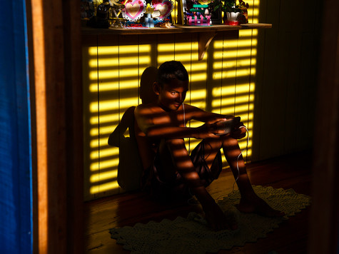 Edielson aproveita o pouco de bateria que tem para jogar enquanto a comunidade aguarda o funcionamento do gerador.  Comunidade Arraiol, Bailique - AP - Brasil.