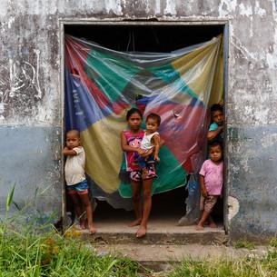 Na estrutura abandonada que se tornou casa temporária para a família, os irmãos colombianos aguardam os pais voltarem de um dia de trabalho.  São Gabriel da Cachoeira, AM - Brasil.