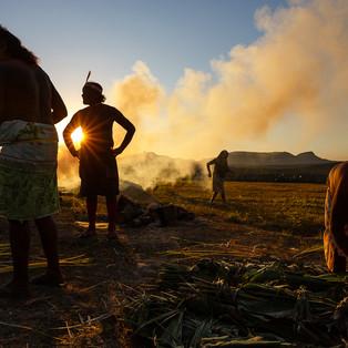 Momentos mágicos durante a preparação da fogueira para o Paparuto.  Paparuto é um prato festivo feito pelas mulheres do povo Krahô. Folhas de bananeira formam a base para um grande envoltório que depois é recheado com mandioca ralada, carne, banana ou peixe. Uma vez selado, o envelope é enterrado e coberto por rochas que foram previamente aquecidas em uma fogueira, cozinhando por quase 12 horas abaixo do solo.  Povo Krahô, TO - Brasil.