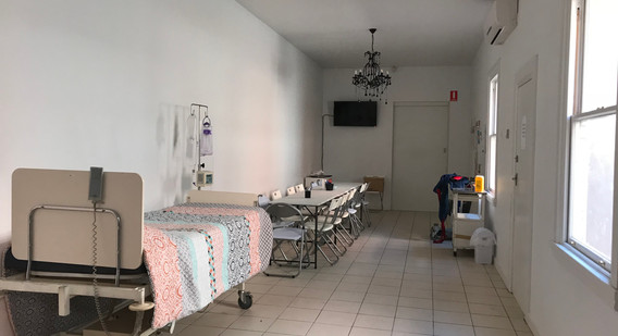 Picture of training room with a bed on one side and a table and chairs.