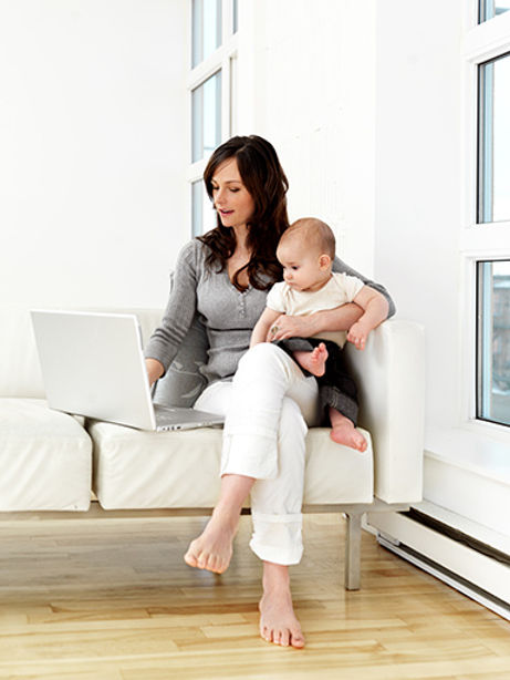 Mother with baby using laptop computer