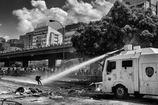 Manifestante es atacado por ráfaga de agua lanzado por ballena de la Policia Nacional Bolivariana. Caracas 2017
