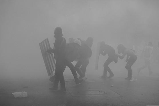 Manifestantes bajo una nube de gas lacrimógeno en Chacaito. Caracas 2017