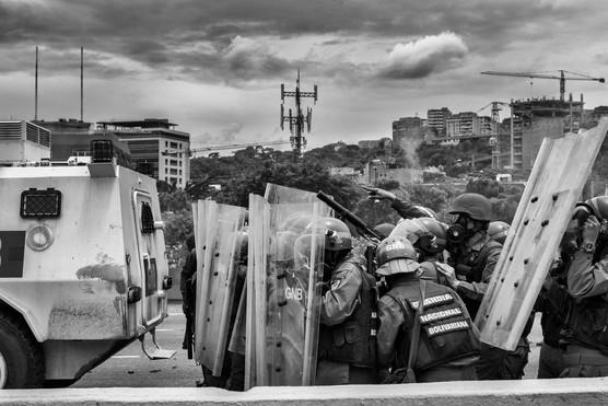 Efectivos de la Guardia Nacional Bolivariana en agrupados avanzan en enfrentamiento contra manifestantes. Caracas 2017