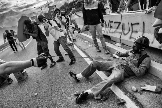 """Manifestantes lanzan piedras con una """"elástica"""" en la autopista Francisco Fajardo. Caracas 2017"""