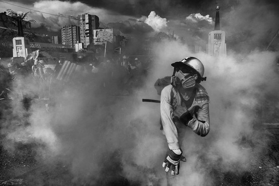 Manifestante lanza una bomba lacrimógena previamente lanzada por la Guardia Nacional Bolivariana. Caracas 2017