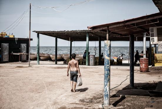 Maikel Soto (13) se dirige al muelle donde trabaja para mantener a su padre que padece la enfermedad de Huntington.  Barranquitas, Zulia. Venezuela. 2015.