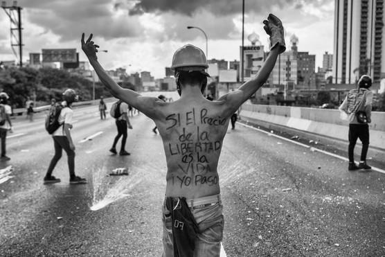 """Mnifestante sin camisa en la autopista Francisco Fajardo con escrito en su espalda """"si el precio de la libertad es la vida yo la pago"""" Caracas 2017"""