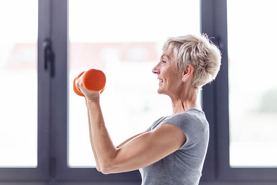 Mature woman exercise with weight on han