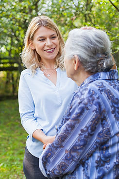Friendly caregiver walking with old lady in the garden - Medical care.jpg