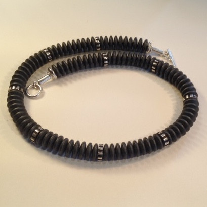 """Charcoal millipede necklace  £250  Frosted, charcoal coloured, Haematite beads and oxidised, ribbed Sterling silver beads make up this 17 1/2"""" long necklace, which also has a handmade Sterling silver catch. This necklace can be made a touch longer or shorter within the price.  Christine Savage 07966550936"""