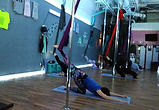 aerial dance and fitness student in aerial yoga sling silks hammock tissue class