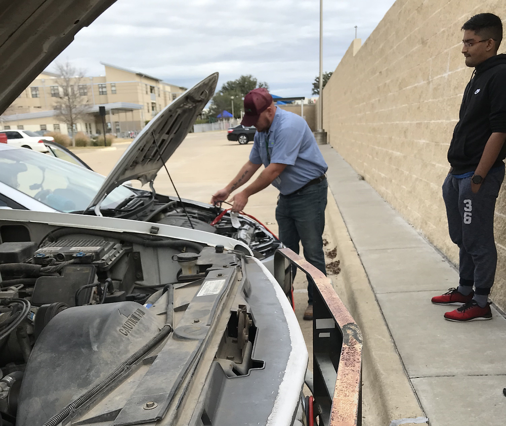 Devin Ayala and Angel Gonzalez help a student in need