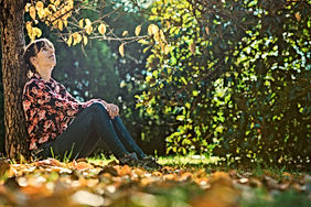 Young woman sitting under an autumn tree