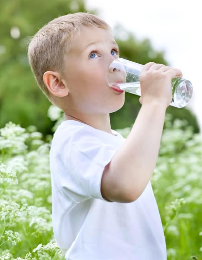 Un enfant bois un verre d'eau. Mais quelle est la vraie qualité de l'eau potable du robinet ?