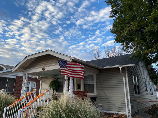 House with American flag with new roof by In His Name Roofing and Construction