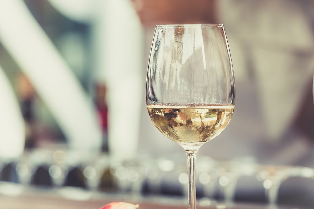 A close up of a wine glass filled with white wine.