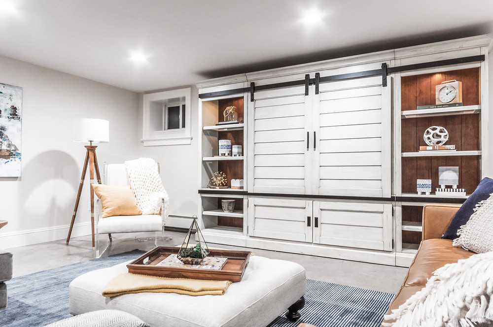 Family room with cream barn door cabinets, a leather sofa, and a white ottoman