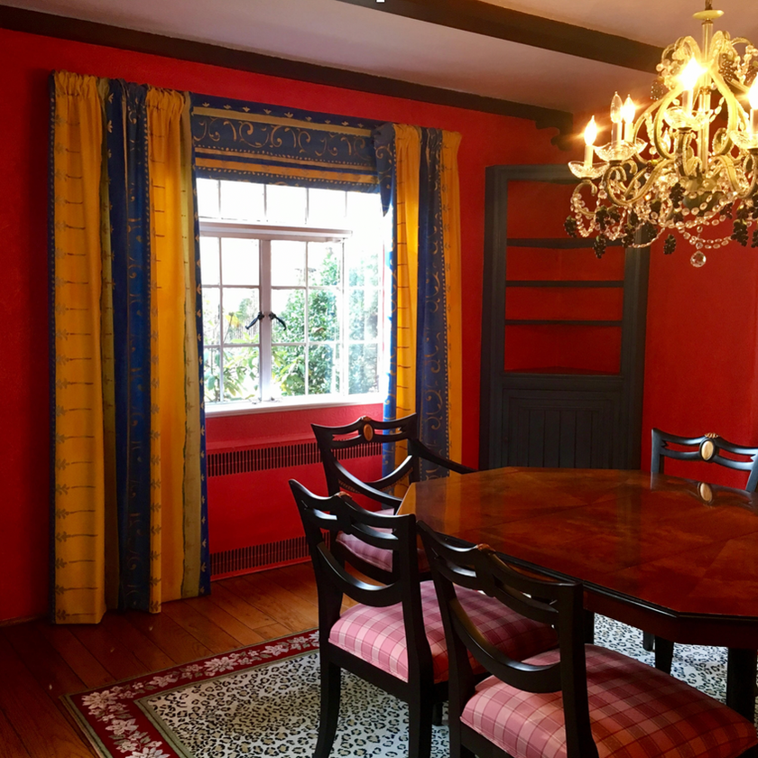 Dark dning room with red wall and traditional dining table and chairs in Tudor home