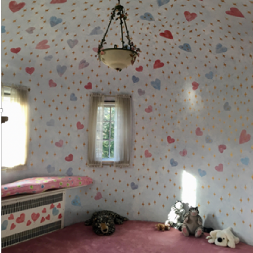 Kids room with pink and purple heart wallpaper in Tudor home