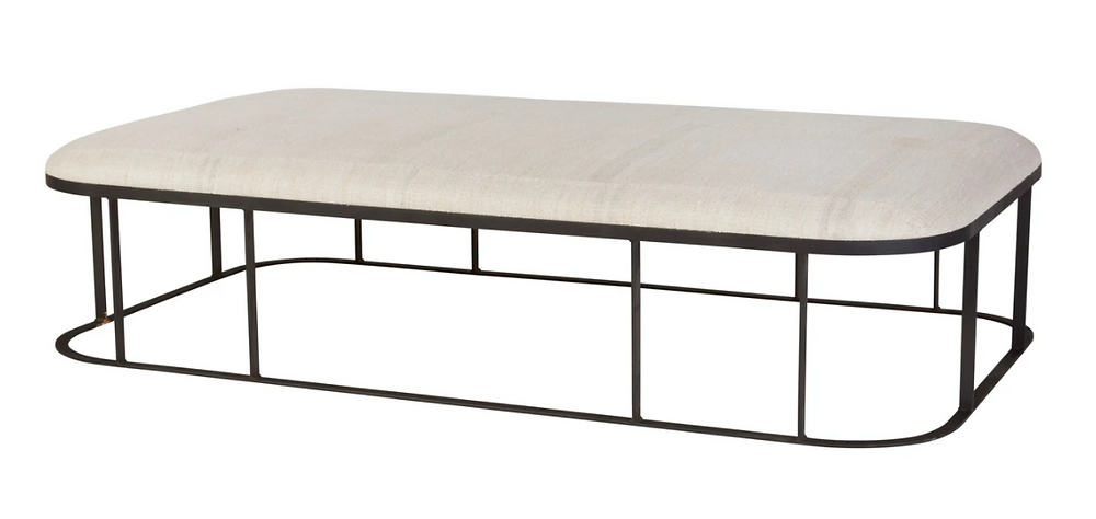 rectangular upholstered coffee table with round edges and a metal base from Cisco Home