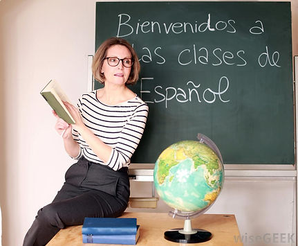 teacher-near-chalkboard-with-spanish-gre
