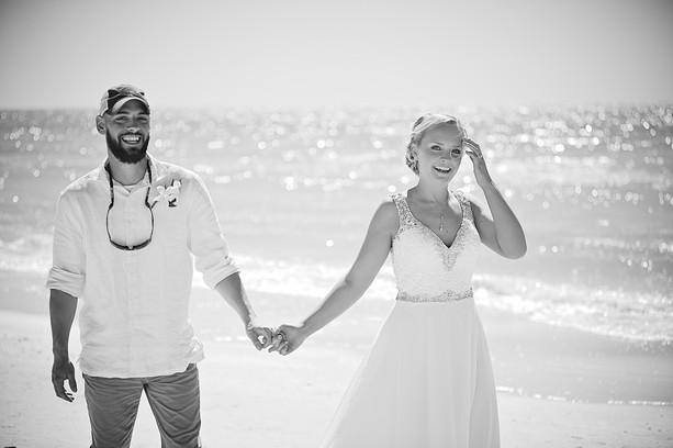 Happy bride and groom walking on Siesta Beach after their wedding.