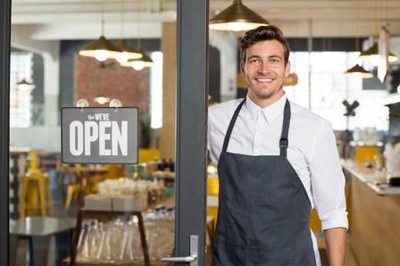 Portrait of smiling owner standing at hi