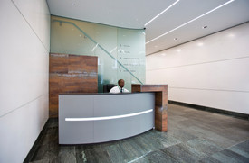 Alma leather wrapped curved reception desk with recessed LED lighting strip and Rusty effect tile over-rider