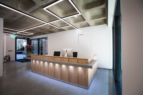 L shaped reception counter finished in panelled crown-cut American White Oak Veneer and dark Grey Micro Concrete