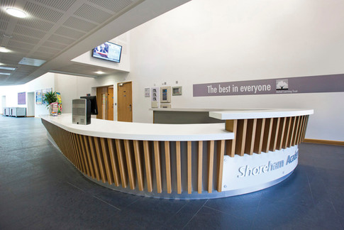 Reception desk in White Hi-Macs solid surface with Oak Veneer timber fins