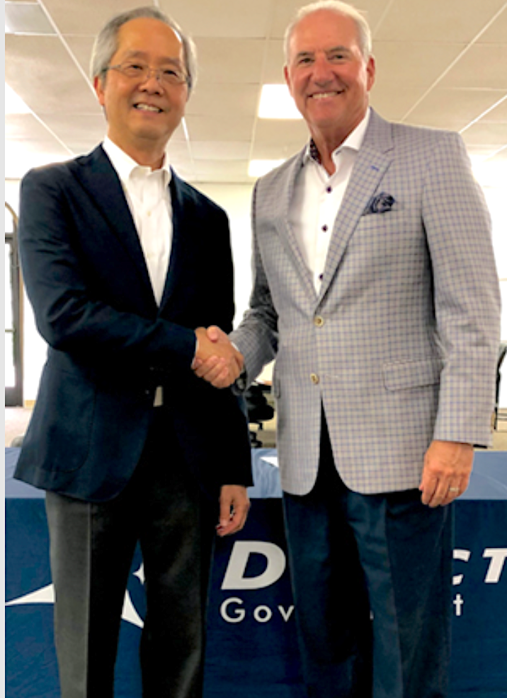 Glowlink's Jeffrey Chu (left) and iDirect Government's John Ratigan shake hands regarding the acquisition