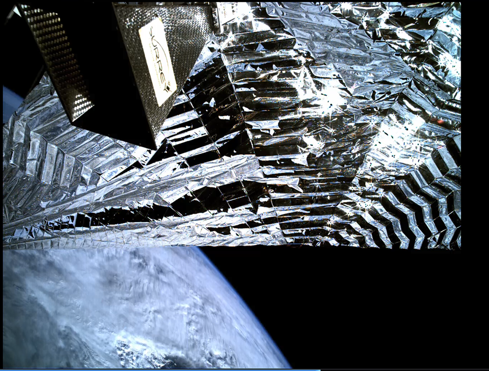 Image acquired by the inspection camera on board TechDemoSat-1 showing the Icarus-1 sail deployed with a view of Earth beyond. The equipment top left is the satellite's Antenna Pointing Mechanism. Credit SSTL