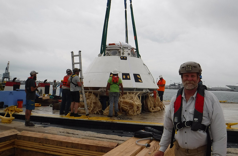 Jon Wootten, a member of the General Dynamics HOOK3 radio technical team, stands in front of the mock NASA capsule before the simulated search and rescue training mission.