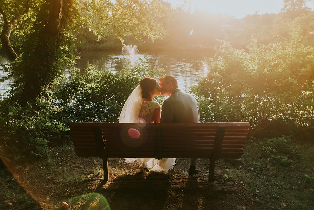 Newly wed couple embrace on a sunny park bench