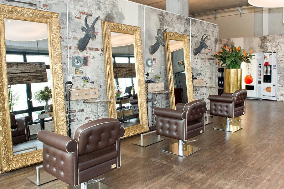 AlpenSonne Coiffeur Innenaufnahme. Ausstattung einer Alphütte mit hohen Räumen, goldige Spiegel, Hirschköpfe und Tapetten im Look einer alten Steinmauer