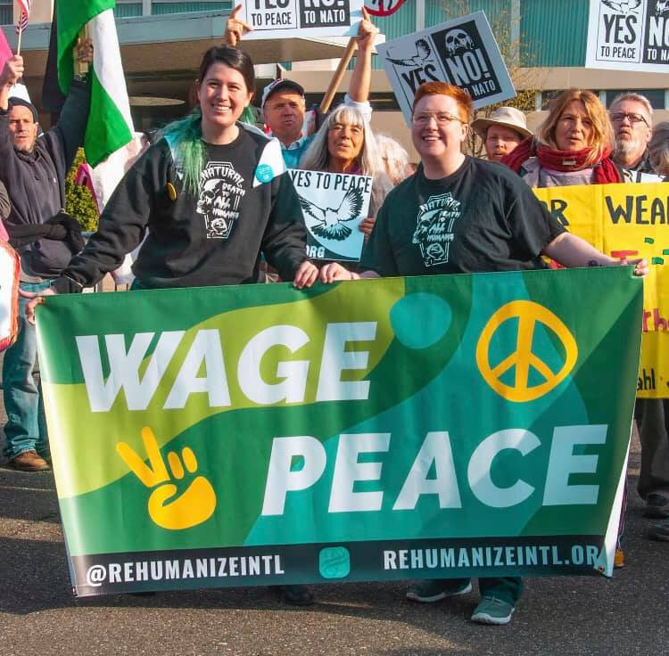"Aimee and Herb holding up a ""Wage peace"" banner in 2019"
