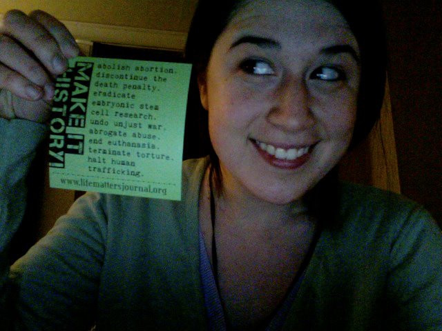 Aimee in 2011 holding up a green Life Matters Journal sticker