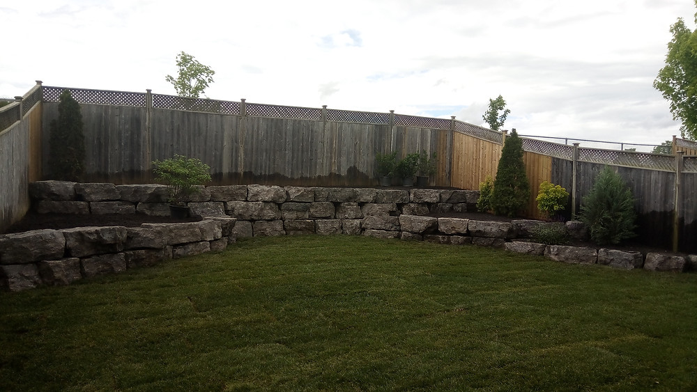 Full redone Backyard landscape with armor stone retaining walls in North Oshawa