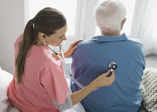 A nurse using a stethoscope on an elderly man in an assisted living facility