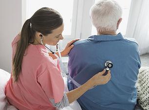 Home Nurse Examining Patient