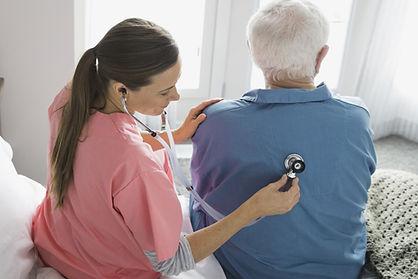 Nurse using stethoscope on mans back