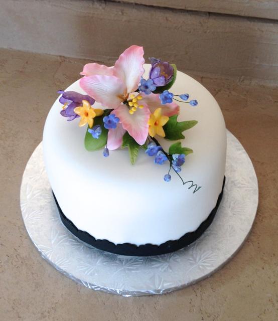 Birthday white fondant with flower spray.png