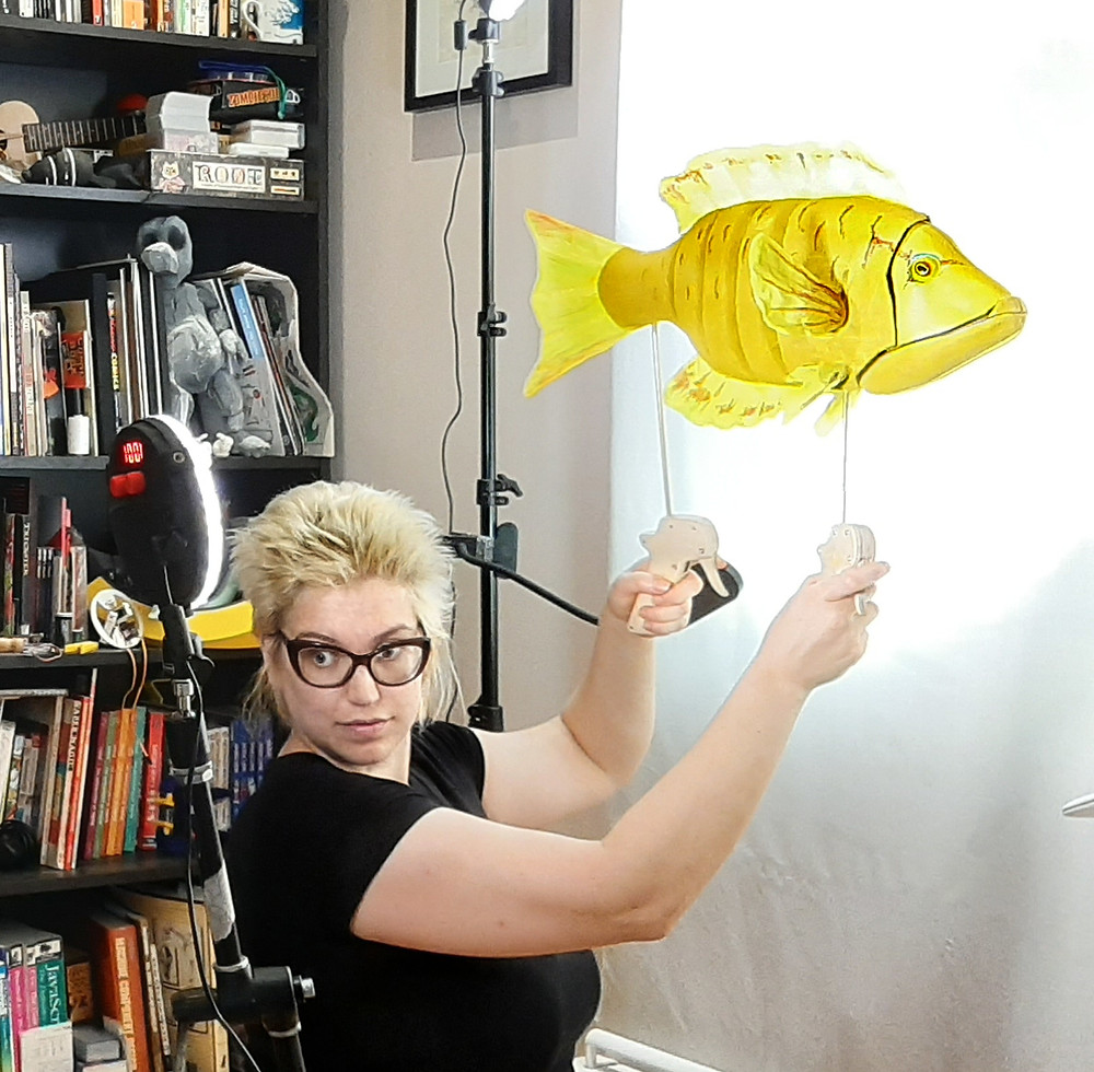 A white puppeteer with short blonde hair and black glasses wearing a black t-shirt holds a slingjaw wrasse yellow fish rod puppet against a screen.