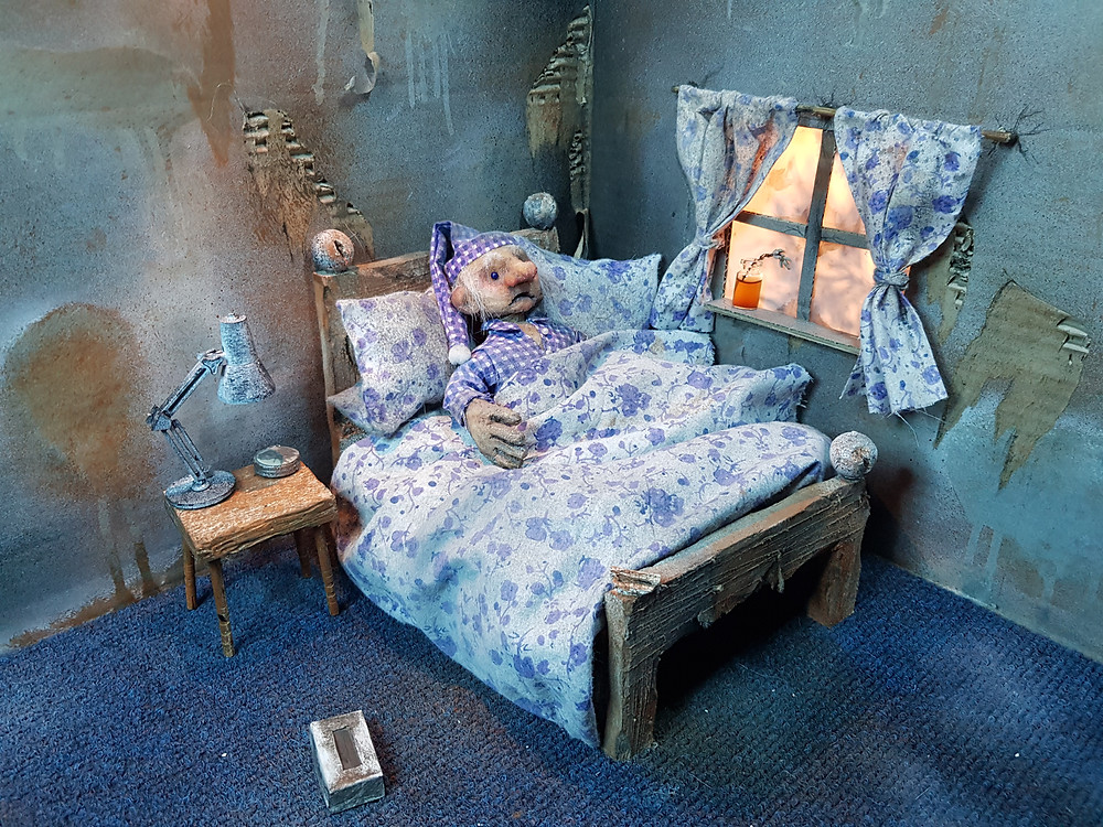 A puppet film set. A puppet lies in bed wearing a nightcap. The room has a blue carpet and flowery curtains line the window. A box of tissues like on the floor next to a bedside table with a lamp on it.
