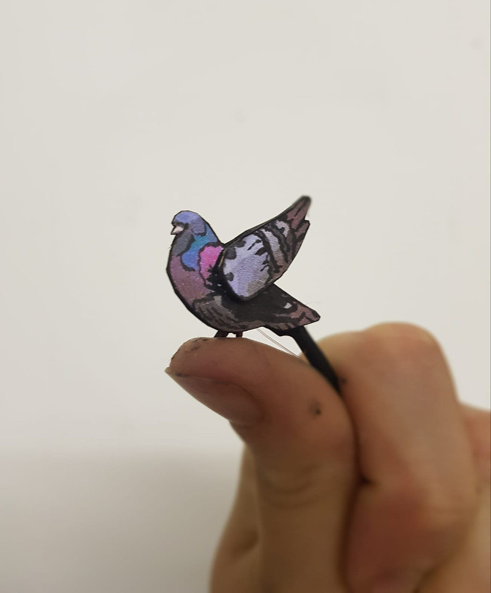A tiny 2cm pigeon puppet with moving wings is held between a puppeteer's fingertips. The pigeons is grey with blue and pink highlights and it's wing points into the air.
