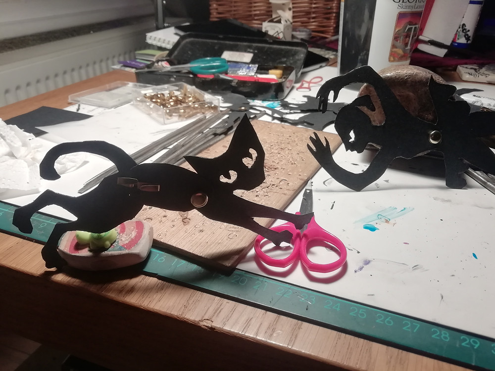 A black cat shadow puppet is propped up on some red scissors in the foreground of the puppet makers workstation. A mermaid puppet can be seen propped up in the background.