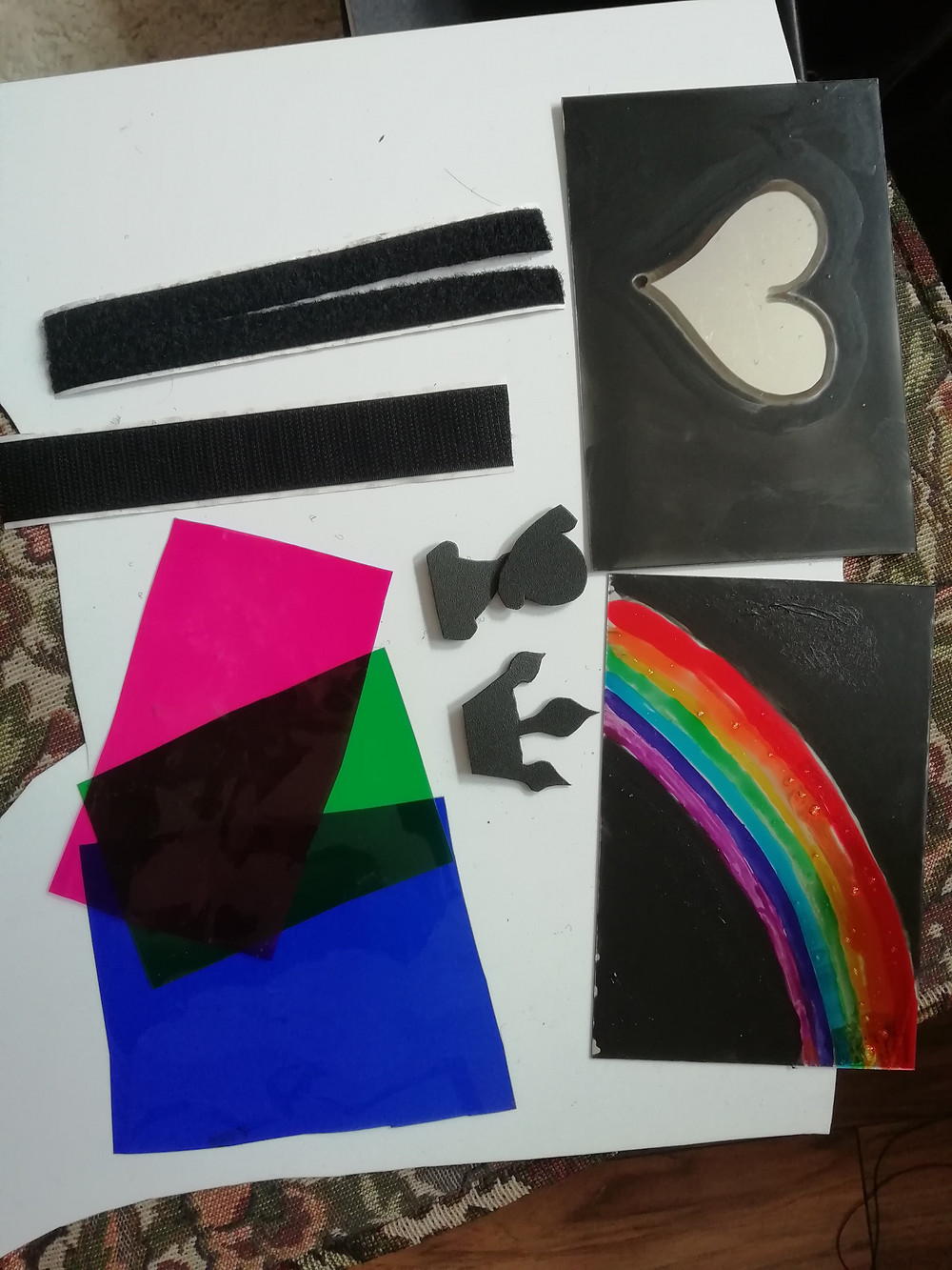 Some of the contents from the shadow kits are laid out on a table, including coloured acetate in pink, green and blue; a heart-shaped cut out and a painted rainbow.