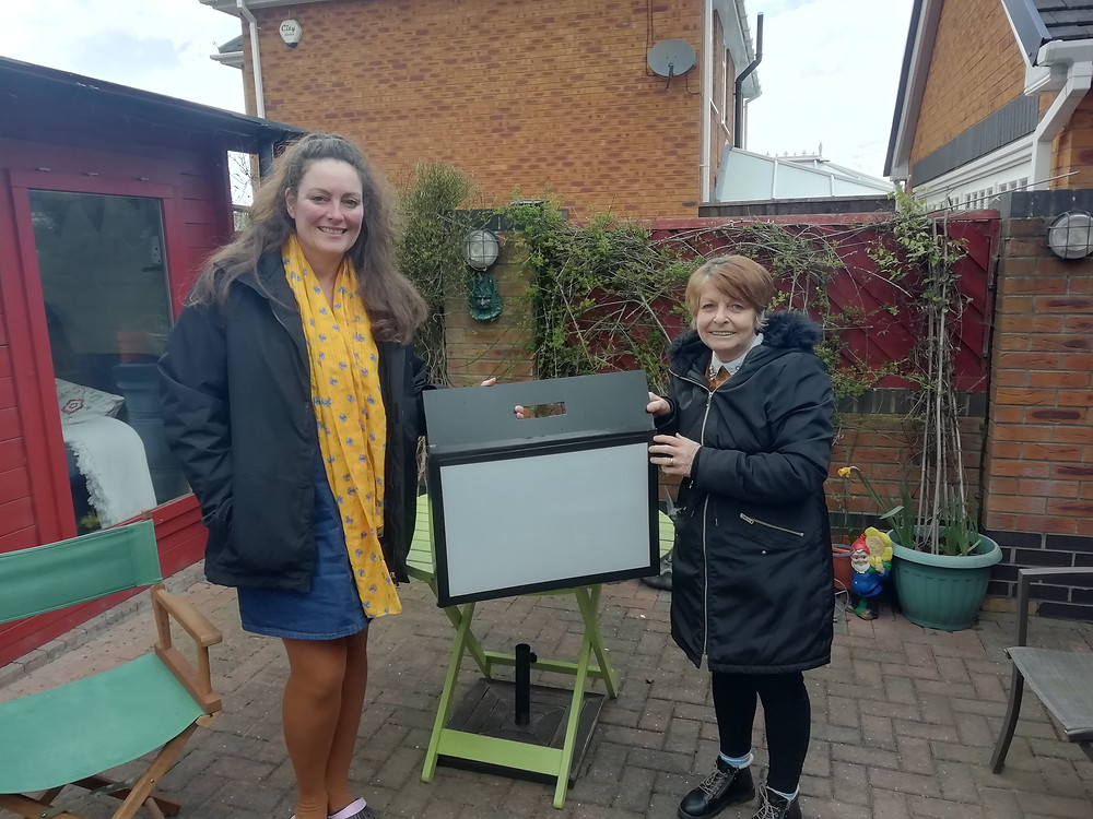 Two participants of the project hold a shadow theatre kit in a garden. One participant who white with long hair and wearing a yellow scarf is from a participating school. The other person is white with short hair wearing a black coat and is from a participating care home.